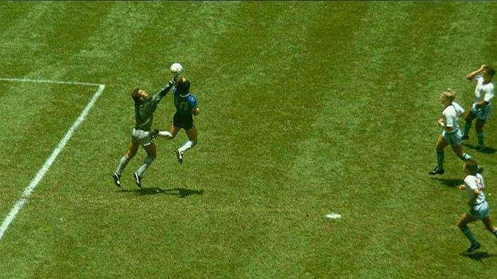 Diego Maradona saat memperdayai kiper Inggris Peter Shilton dengan tangannya yang mencetak gol 'Tangan Tuhan'.