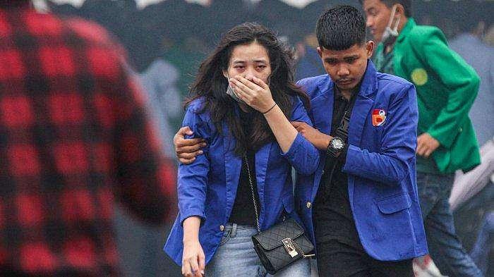 Seorang mahasiswa terkena gas air mata saat bentrok dengan anggota kepolisian di depan gedung DPRD Sumatera Selatan, Jalan POM IX, Palembang,Kamis (8/10/2020). Mahasiswa melakukan aksi demo untuk menolak Undang-undang Omnibus Law Cipta Kerja, Aksi Demo mahasiswa ini berujung bentrok dengan aparat keamanan yang mengakibatkan sejumlah fasilitas umum dan kendaraan milik polisi rusak.