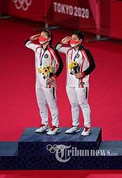 Atlet Indonesia Apriyani Rahayu (kanan) dan Greysia Polii Indonesia memberi hormat dengan medali emas bulu tangkis ganda putri pada upacara Olimpiade Tokyo 2020 di Musashino Forest Sports Plaza di Tokyo. Senin (2 Agustus 2021). (Pedro PARDO/AFP)