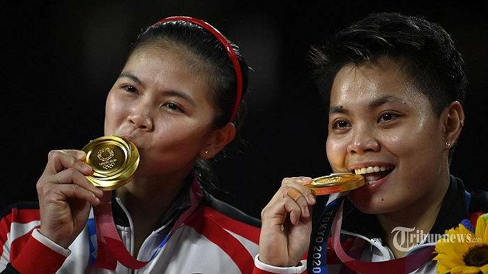 Atlet Indonesia Apriyani Rahayu (kanan) dan Greysia Polii Indonesia berpose dengan medali emas bulu tangkis ganda putri mereka pada upacara selama Olimpiade Tokyo 2020 di Musashino Forest Sports Plaza di Tokyo pada 2 Agustus 2021. (Alexander NEMENOV/AFP)