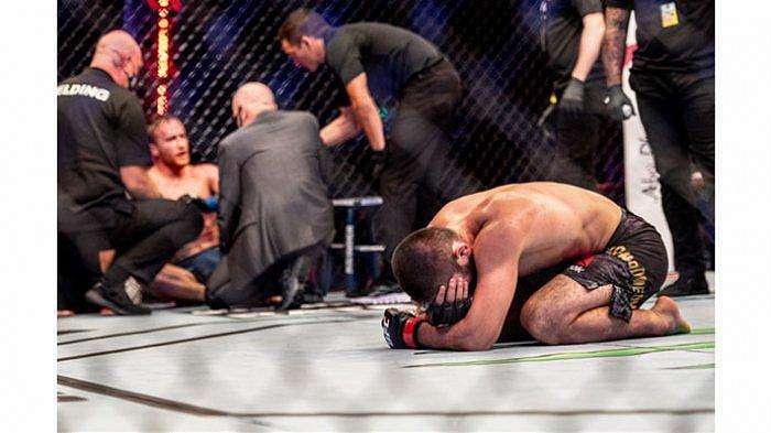 Petarung kelas ringan UFC, Khabib Nurmagomedov, bersujud setelah berhasil memenangkan pertarungan melawan Justin Gaethje pada ajang UFC 254, Minggu (25/10/2020).