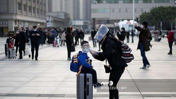 Seorang wanita mengenakan masker menyesuaikan masker anaknya ketika mereka tiba di Stasiun Kereta Api Hankou di Wuhan untuk mengambil salah satu kereta pertama yang meninggalkan kota di provinsi Hubei tengah Cina awal pada 8 April 2020