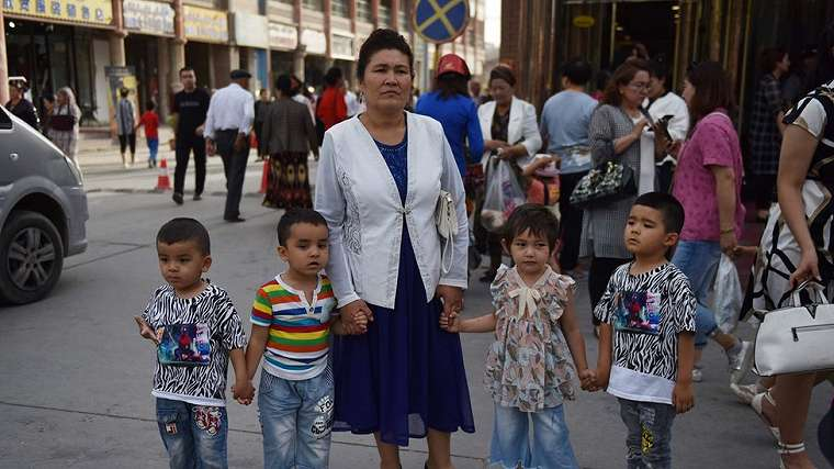 This file photo taken on June 4, 2019 shows a Uighur woman waiting with children on a street in Kashgar in China`s northwest Xinjiang region.