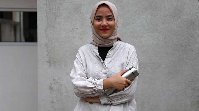 Astri Puji Lestaria stands outside her home in Jakarta holding a re-usable water bottle.