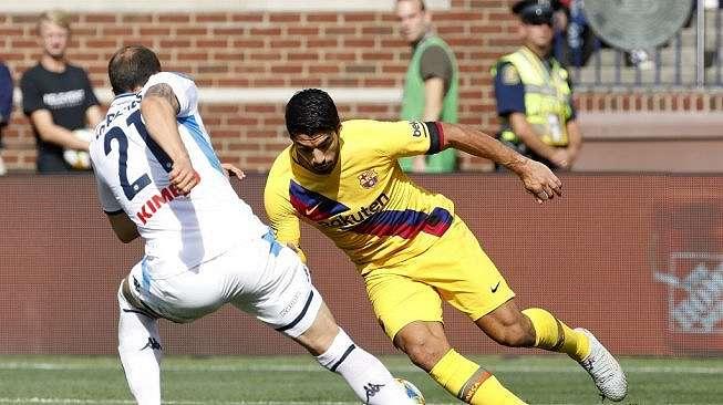 Penyerang Barcelona, Luis Suarez menggocek pemain Napoli pada laga persahabatan di Stadion Michigan, Amerika Serikat, Minggu (11/8/2019). (JEFF KOWALSKY / AFP)