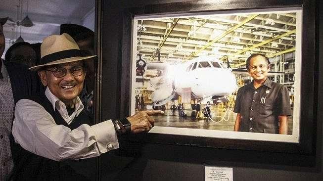 Mantan Presiden BJ Habibie menunjukan foto dirinya bersama pesawat hasil karyanya N-250 Gatotkaca usai membuka pameran foto Cinta Sang Inspirator Bangsa Kepada Negeri di Museum Bank Mandiri, Jakarta, Minggu (24/7/2016). [Antara/Muhammad Adimaja]
