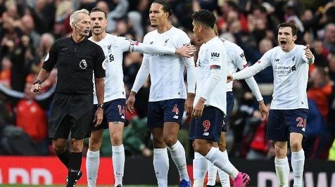 Para pemain Liverpool sempat memprotes keputusan wasit Martin Atkinson (kiri) saat laga melawan Manchester United dalam lanjutan Liga Inggris di Old Trafford. Oli SCARFF / AFP