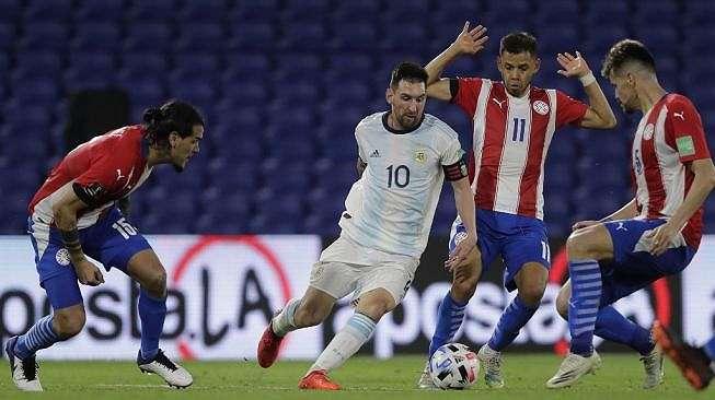Kapten Timnas Argentina, Lionel Messi (tengah) dikepung para pemain Paraguay dalam laga kualifikasi Piala Dunia 2022 zona Amerika Latin di La Bombonera, Buenos Aires, Argentina, Jumat (13/11/2020) pagi WIB. [Juan Ignacio RONCORONI / POOL / AFP]