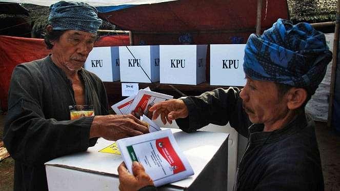 Warga Baduy Luar dibantu petugas TPS memasukan kertas suara usai melakukan pencoblosan dalam Pemilu 2019 di TPS 01 di Desa Kanekes, Lebak, Banten